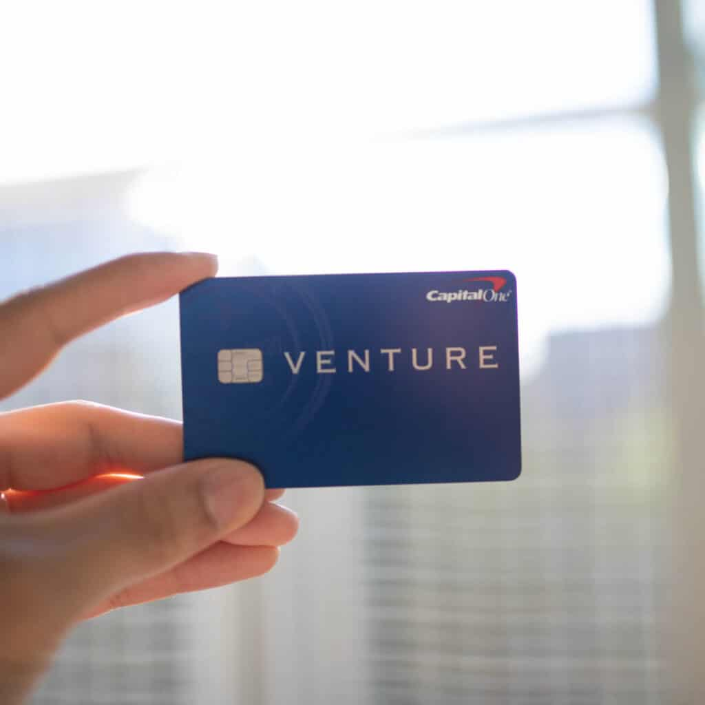 Hand holding the Capital One Venture card.