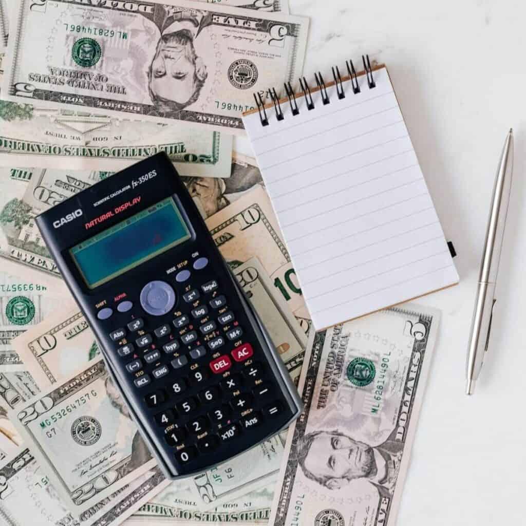 Cash beneath a calculator, notepad, and pen.