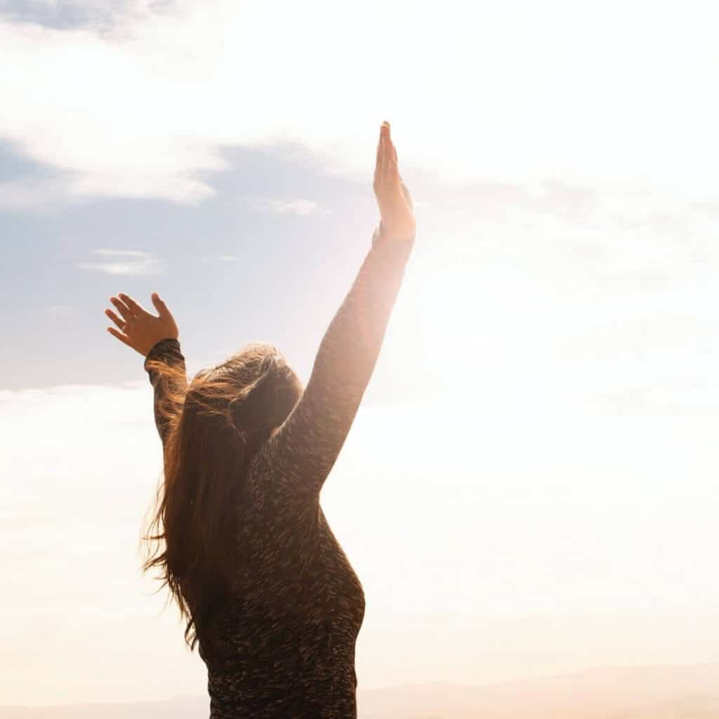 Person raising their arms to the sky.