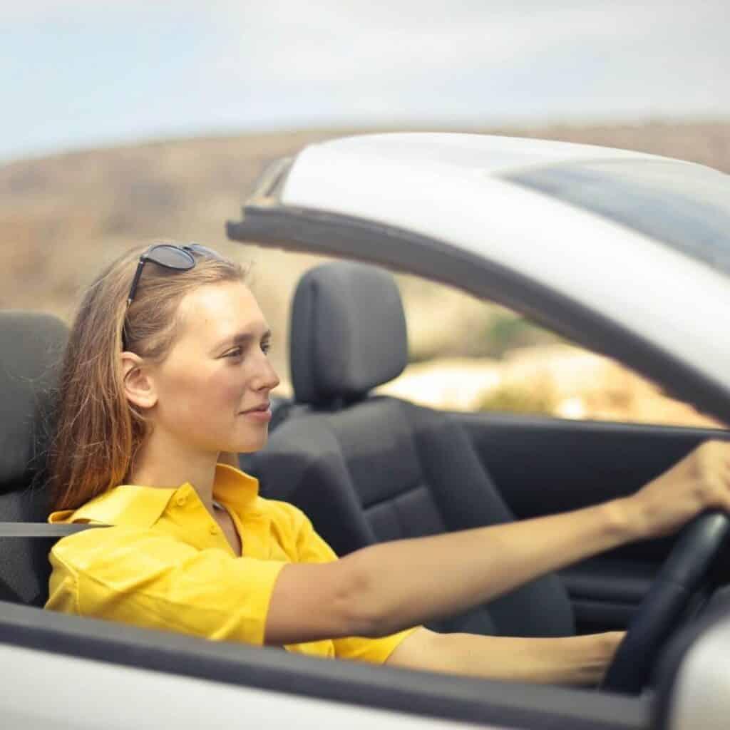 Person driving a convertible car.
