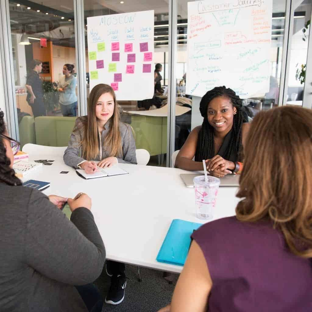 Group of people meeting at a table in a conference room.