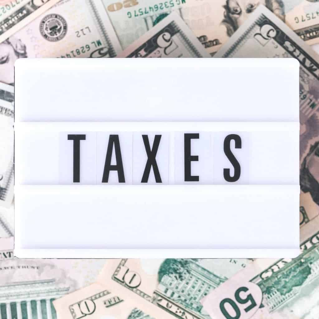 """Money underneath a retro light box with the word """"taxes"""" spelled on it."""