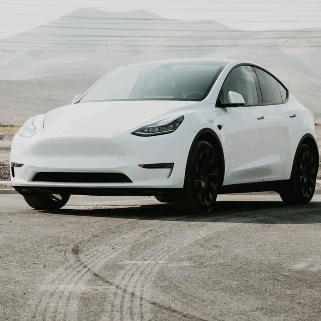 White Tesla Model Y with mountains in the background.