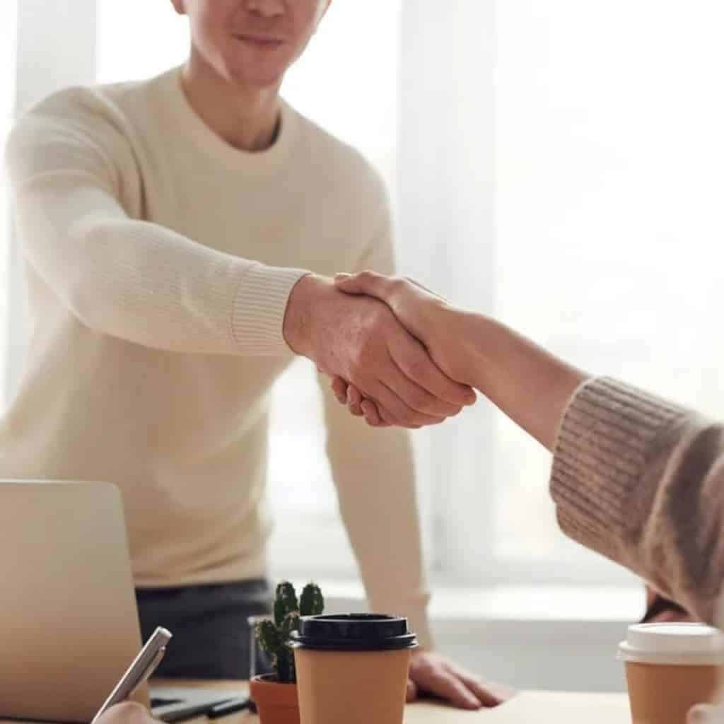 Close-up of two people shaking hands at a table.