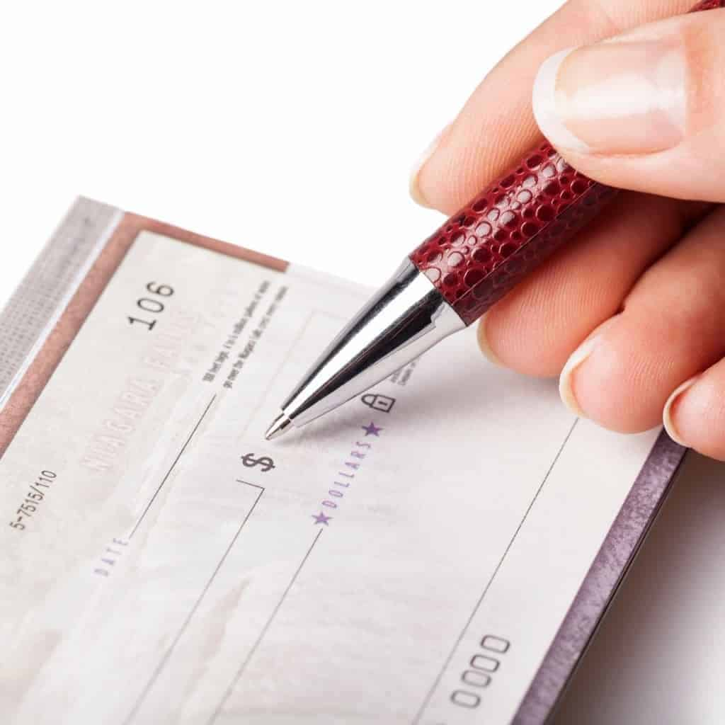 Close-up of a person writing a check.