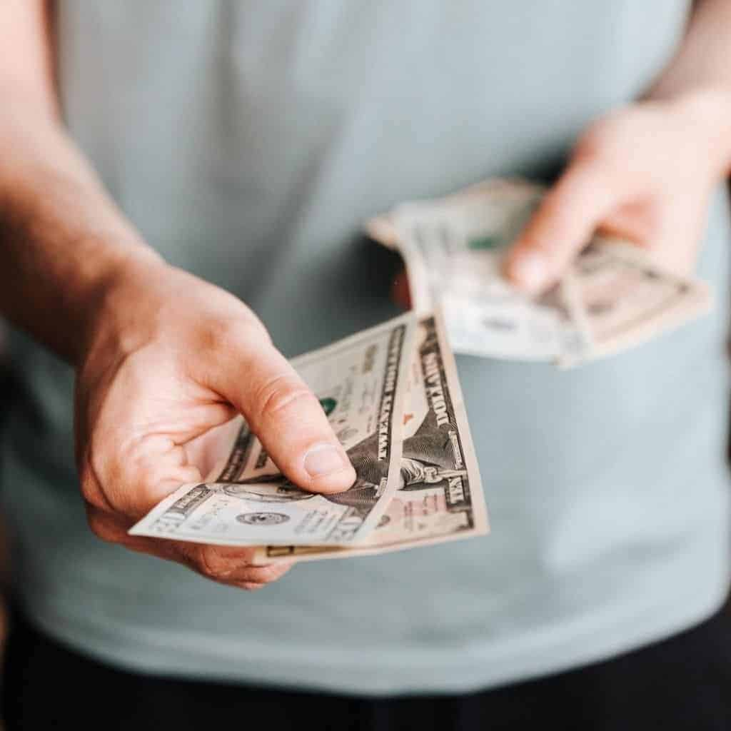 Close-up of a person handing out cash.
