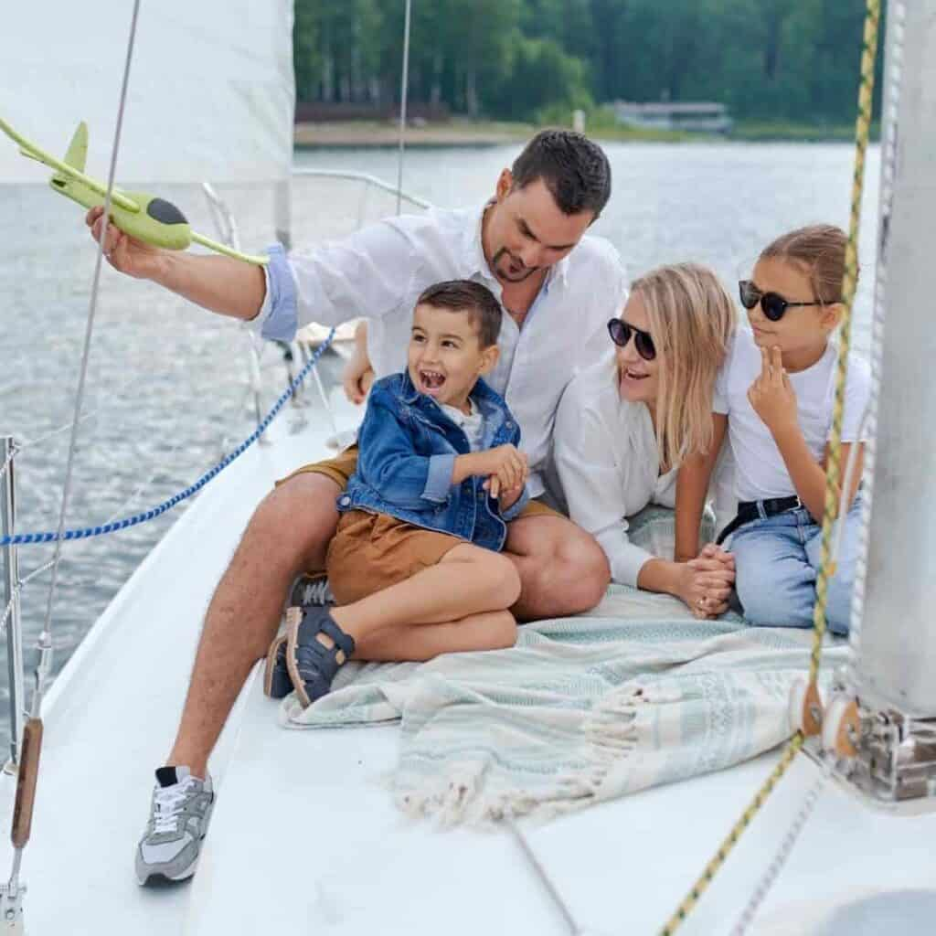 Family sitting on a boat in the water.