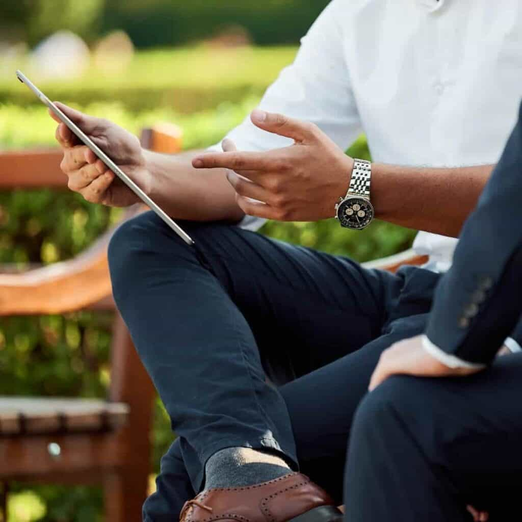Person sitting on a bench outdoors and pointing at their tablet.