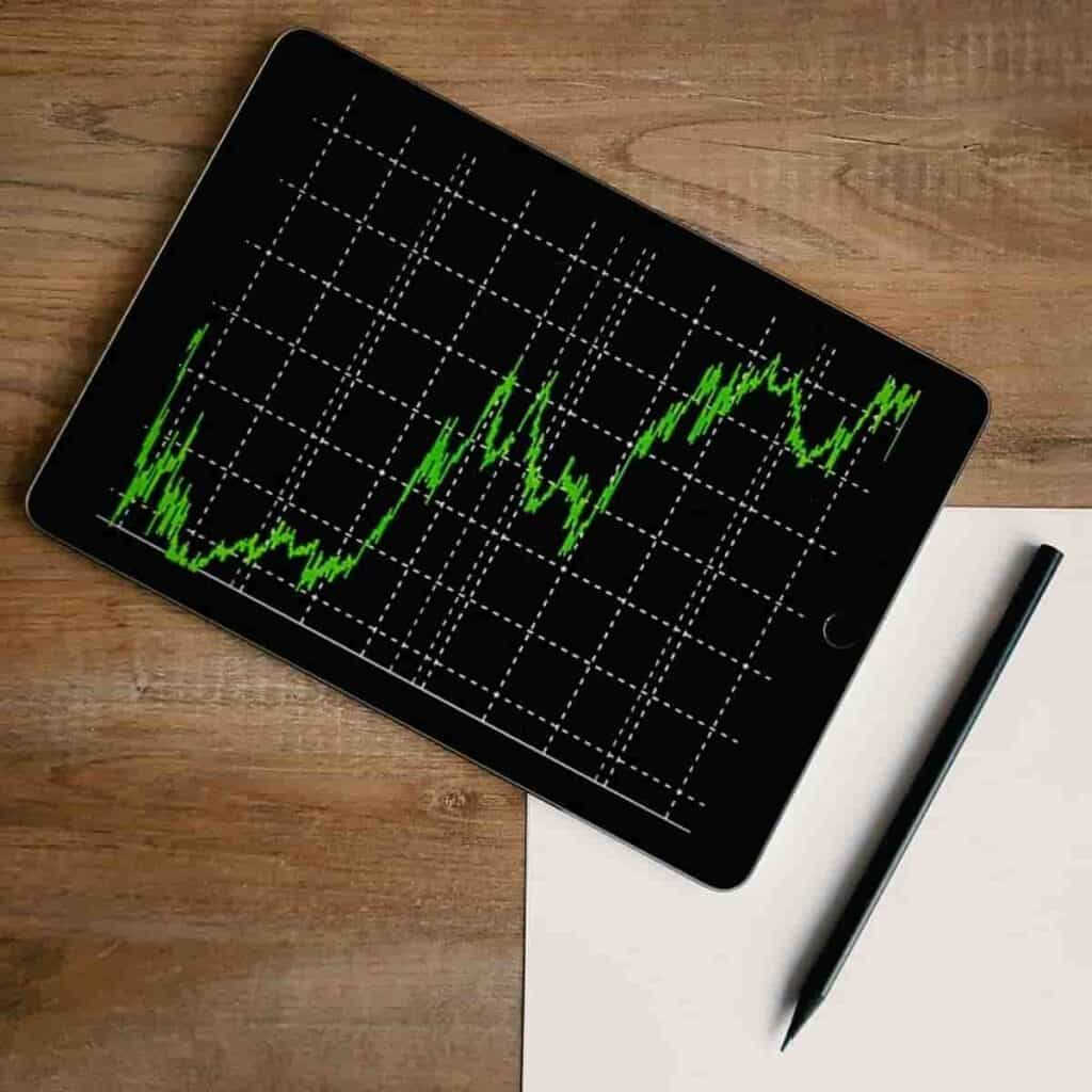 Tablet on a table showing a chart, next to a pen and paper.