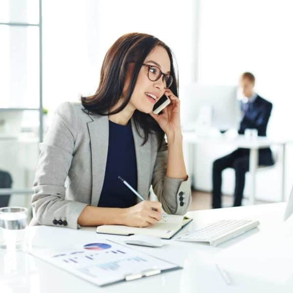 Business person sitting at a desk and writing while talking on the phone.
