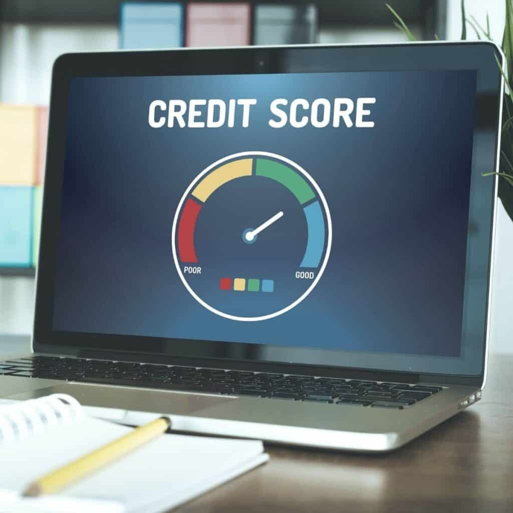Laptop on a table showing a credit score range on the screen.