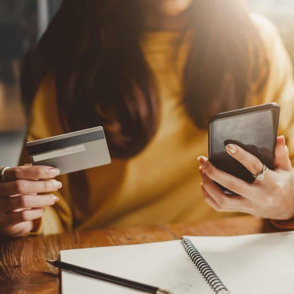 Person sitting at a table and holding a credit card and a phone.