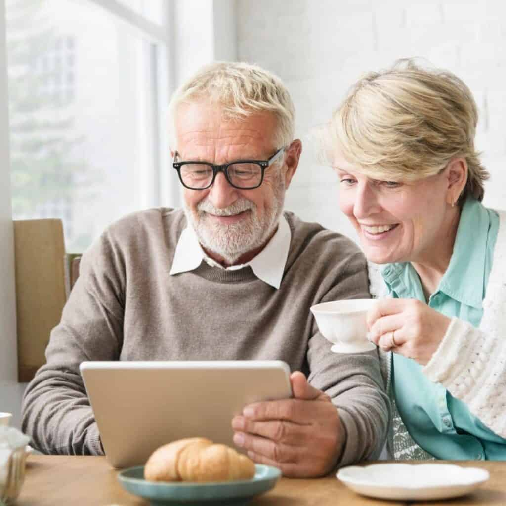 Retired couple looking at a tablet and drinking a cup of coffee.